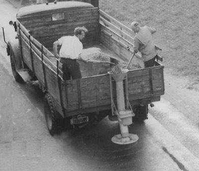 Streuen anno 1956 - Zwei Männer schaufeln auf der Ladefläche eines LKWs stehend Streugut über die offene Ladekante